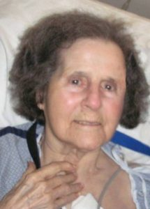 Photo of an elderly woman with gray hair and pale skin, lying back against a pillow and smiling slightly. She is wearing a hospital gown.