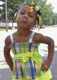 Photo of Kendrea Johnson. She is an African-American girl wearing a yellow dress, her hair in hair clips. She has her hands on her hips and is leaning forward, lips puckered, as though she is trying to kiss the camera.
