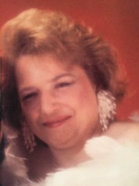 Photo of Rosemary Vincent. She is a middle-aged woman with a round face, pale skin, and short curly red hair. She is wearing big white feathered earrings.