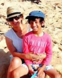 Photo of Liam Milne and his mother Susana. Liam is a light-brown-skinned boy with curly black hair, wearing a baseball cap and pink shirt. His mother is a woman with brown hair and pale skin, wearing sunglasses and a straw hat. She has her arms around Liam.