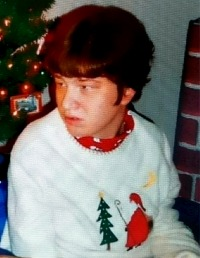 Photo of Courtney Liltz, a young woman with short, curly brown hair and fair skin. She wears a Christmas sweater.
