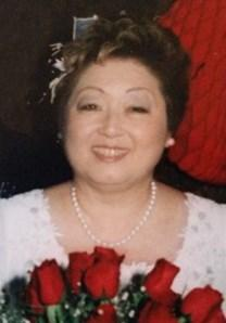 Photo of Margaret Yamaguchi, a middle-aged Asian woman wearing a white dress and holding a bouquet of red roses.
