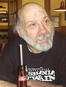 Photo of Richard Brichacek. He is an elder wearing a black T-shirt. He has fair skin with some age spots, and is bald with a bushy white mustache and beard. There is a beer bottle with a straw in it on the table in front of him.