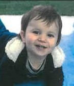 Photo of a toddler boy in a winter coat, lying on his stomach and looking at the camera.