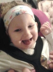 Photo of a baby girl with curly blond hair tied in a headband, strapped into a car seat. She is smiling.