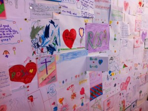 Bulletin board covered with children's drawings with Dutch text, memorializing Lucas and Rosa.