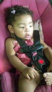 Photo of Saharah Weatherspoon, a toddler girl sitting in a pink car seat. She has very curly black hair and brown skin.