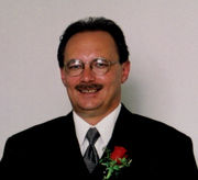 Photo of Ronald McCabe. He is a middle-aged man wearing glasses and a suit with a rose pinned to the lapel. He has fair skin, dark brown hair and a mustache.