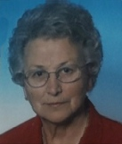 Portrait photo of Luciana Torcelli; she is an elderly woman with curly gray hair and fair skin. She is wearing a red blouse and glasses.