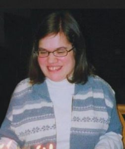 Photo of Melissa Couture, a young woman with fair skin and brown hair. She is wearing glasses and a striped sweater. She is smiling broadly and looking down at some candles.