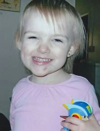 Photo of Brielle Gage, a toddler girl with very light, straight hair, wearing a pink t-shirt and holding a colorful toy. There is a small bruise on her chin.
