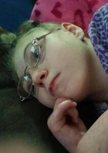 Photo of a teenage girl wearing glasses, lying down, her chin in her hand.
