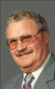 Photo of Harold Ambrosius, a white man with graying hair and mustache. He is wearing a suit and tinted glasses.