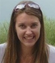 Photo of Abigail Cozad. She is a young woman with fair skin and long straight brown hair; she has a pair of glasses pushed up on top of her head.