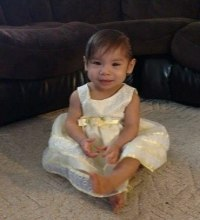 Photo of Kira Friedman. She is a toddler with straight brown hair and tan skin. She is barefoot, wearing a fancy white dress.