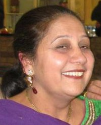 Photo of Jagtar Gill, a middle-aged woman with light brown skin and dark brown hair, wearing make-up, earrings, and a brightly colored green and purple top.