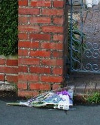 Flowers left at Jean Irwin's house. They are purple and white flowers, lying on a curb next to a brick wall and wrought-iron gate.