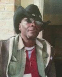 Photo of Cedric Page, an African-American man wearing a cowboy hat, brown jacket, sunglasses, and a small gold cross necklace.