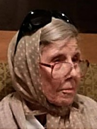Photo of Peggy Sinclair. She is an elderly woman with light skin and gray hair; she is wearing glasses, which are slipping down her nose, and a polka-dotted beige headscarf.