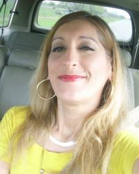 Photo of Noemi Villarreal. She is a woman with pale skin and straight blond hair; she is wearing a yellow shirt, jewelry, and make-up.