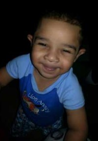 Photo of Princeton Holloway, a toddler boy with tan skin and dark curly hair, photographed from above and looking up at the camera.