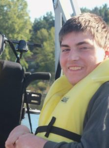 Photo of Theron Leonard. He is a young man with fair skin and short brown hair. He is wearing a gray sweatshirt and a yellow life vest and smiling at the camera.