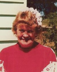 Photo of Joan Vollmer, standing outside her house. She has short curly red hair and fair skin and is wearing a red turtleneck.