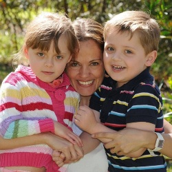 Photo of Maria, Elisa, and Martin Lutz, a mother and two children. Maria is hugging her two children, who are wearing brightly-colored clothing. They are all fair-skinned with light brown hair.
