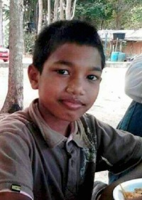 Photo of Mohamad Abdullah, a boy with brown skin and dark brown hair. He is wearing a gray polo shirt.