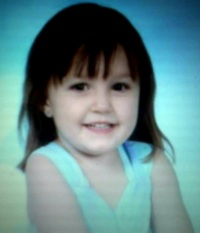 Photo of Gracie Buss, a small girl with fair skin, dark brown eyes, and black hair. She is smiling.