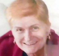 Photo of Laraine Rayner. She is a middle-aged woman with short strawberry-blonde hair. She is wearing hoop earrings and a red sweater.