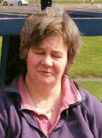 Photo of Sharon Greenop, a middle-aged woman with short brown hair, photographed outdoors. The camera seems to have caught her off guard, since she has her eyes closed mid-blink.
