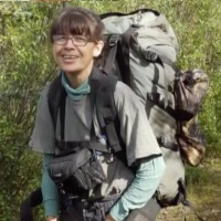 Photo of Riba DeWilde. She is a woman with brown hair, fair skin, and large glasses. She is wearing a large hiking backpack and smiling.