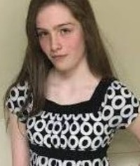 Photo of Natalie Finn, a teenage girl with fair skin and straight brown hair. She is wearing a black-and-white dress and has a solemn expression on her face.