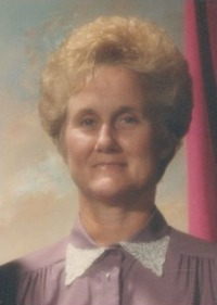 Portrait photo of Phyllis Mansfield, a middle-aged woman with short, permed blond hair, blue eyes, and fair skin. She wears a pink blouse with white collar.