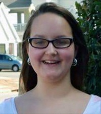 Photo of Grace Packer. She is a teenage girl with fair skin and straight brown hair. She is wearing hoop earrings, black-rimmed glasses, and a white flowered shirt.