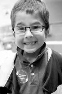 Black and white photo of Seth Johnson, a small boy wearing glasses and a polo shirt and jacket.