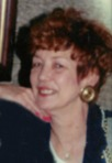 Photo of Barbara Martone. She is a woman with auburn hair and fair skin, wearig pink lipstick and nail polish, gold earrings, and a black and gray blouse.