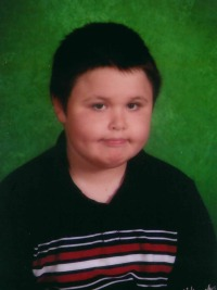 Photo of Joseph Bishop. He is a boy in his young teens, with short-cut dark brown hair and fair skin, wearing a navy-blue sweater.