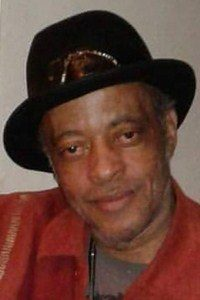 Photo of Walter Clark. He has brown skin; he is wearing a black hat and a red collared shirt.