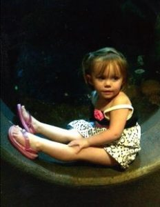 Photo of Bethannie Johnson, a toddler girl in a short black-and-white dress and pink sandals. She has fair skin and short, wispy brown hair; she is sitting sideways on a curved surface and looking at the camera.