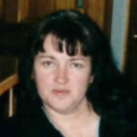 Photo of Cheryl Young, a middle-aged woman with fair skin and long black hair.