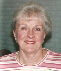 Photo of Ruth Bain, an older woman with pale skin, wearing a red-striped top and pearl earrings. Her hair is short, curly, and nearly white.