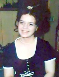 Photo of Perleen Bode. She is a young woman with fair skin and dark curly hair; she is wearing an old-fashioned navy blue dress with white trim.