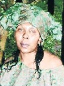 Photo of Refilwe Monamodi. She is a woman with light-brown skin and black hair that has been partly dyed green. She looks about middle aged.