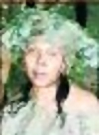 Photo of Refilwe Monamodi. She is a woman with light-brown skin and black hair that has been partly dyed green. The photo is blurry and grainy, but she looks to be around middle age.