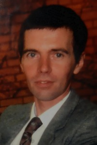 Photo of Paul Roddy, a man with fair skin and dark-brown hair. He is wearing a suit and tie.
