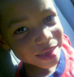 Photo of Kentae Williams, an African-American boy. He is smiling, showing missing front teeth.
