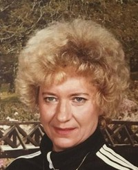 Photo of Charlene Norris. She is a middle-aged woman with short permed blond hair and fair skin, wearing a black and white track suit.