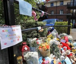 "Memorial left outside Omran Omar's apartment, consisting of flowers, stuffed animals, and notes. In the foreground is a sign that says, ""Rest in peace, precious little boy."""